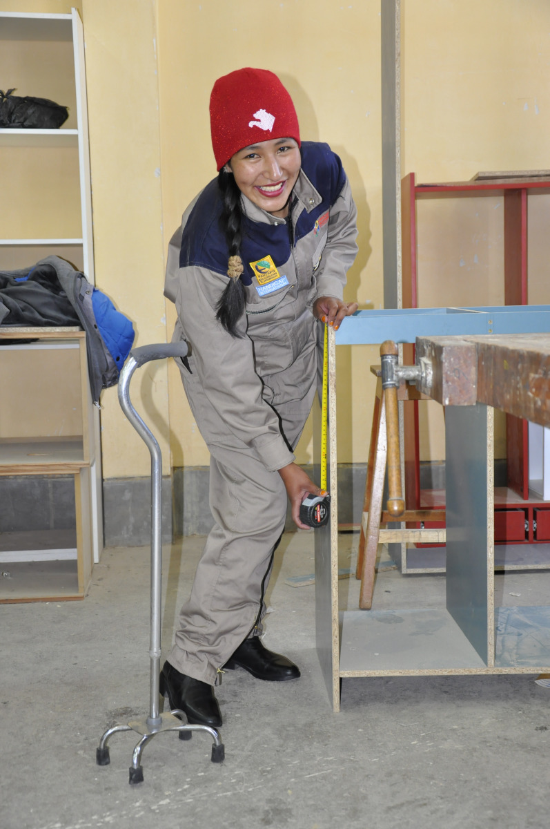 A woman with a disability is using measuring tape to measure the length of a piece of wood in Bolivia