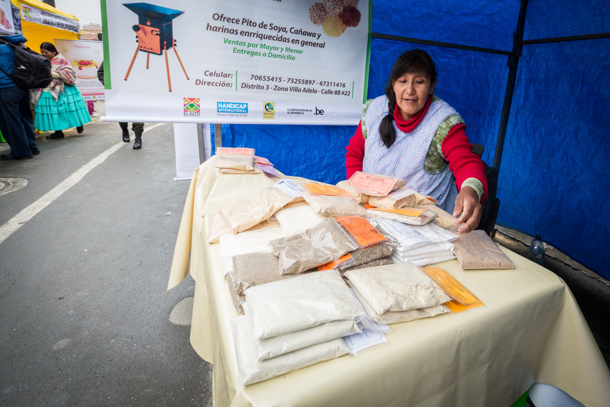 A woman operates a booth selling ground cereal in Bolivia