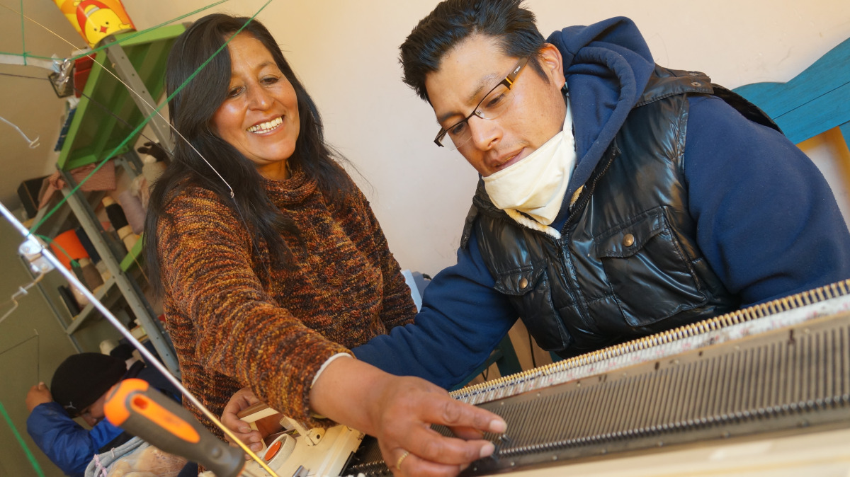 A man with a disability is being shown how to use a machine to knit by a woman in Bolivia