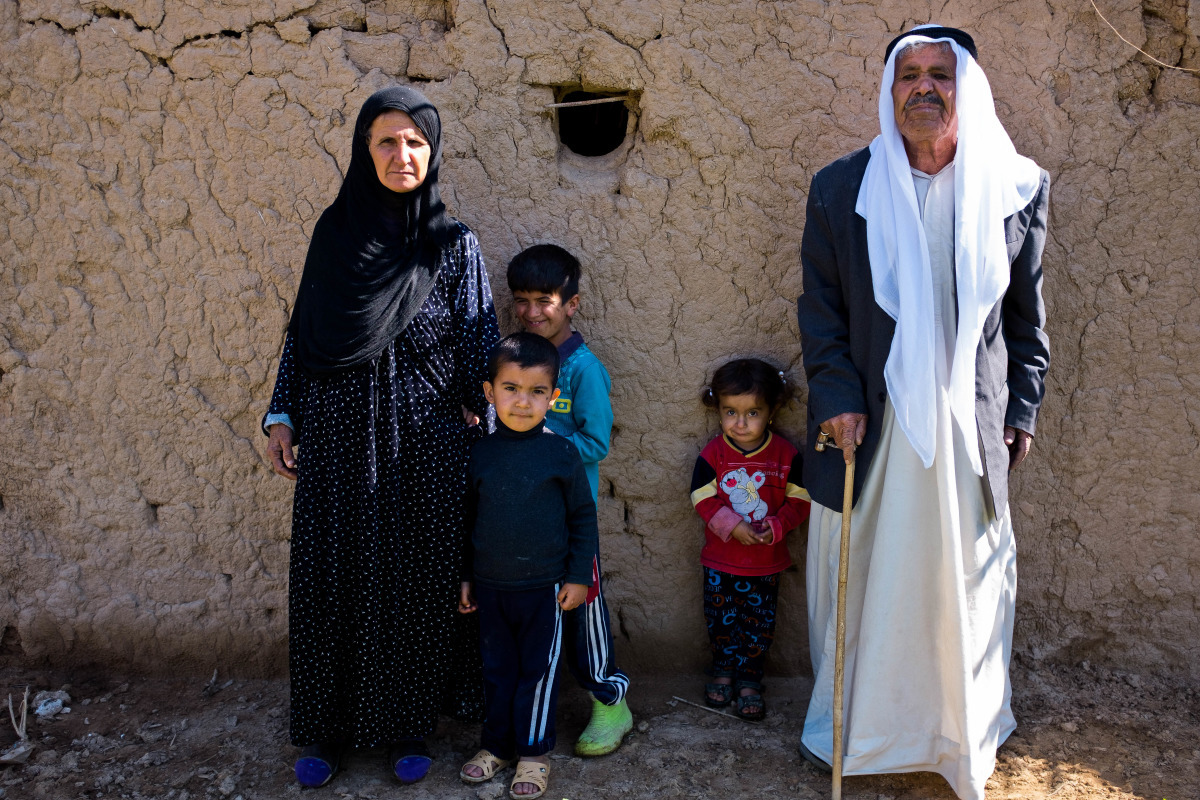 An older man and older woman stand next to three young children outside in Iraq.