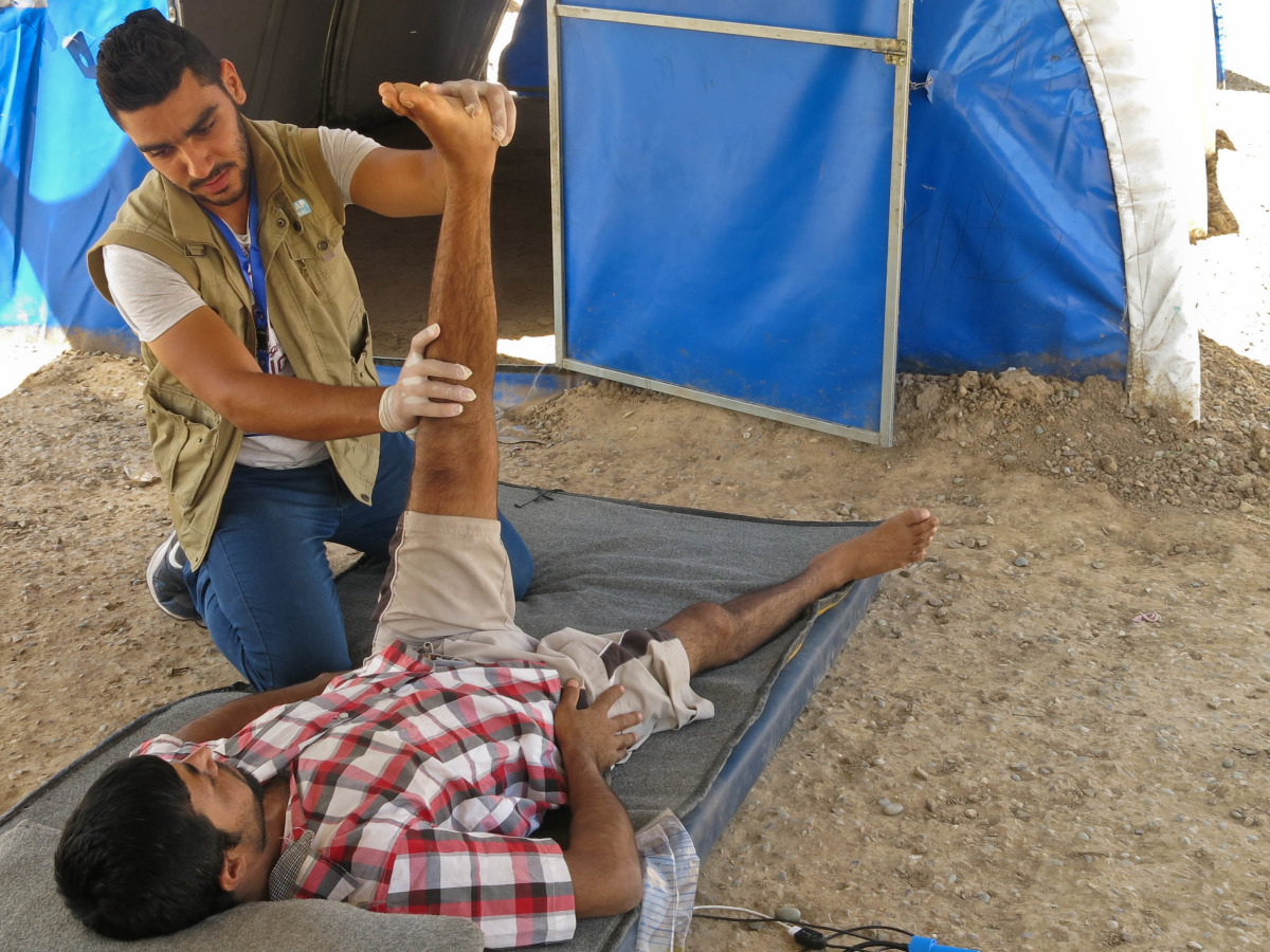 A physical therapist with Handicap International does exercises with an injured Iraqi man at an IDP camp in Iraq.