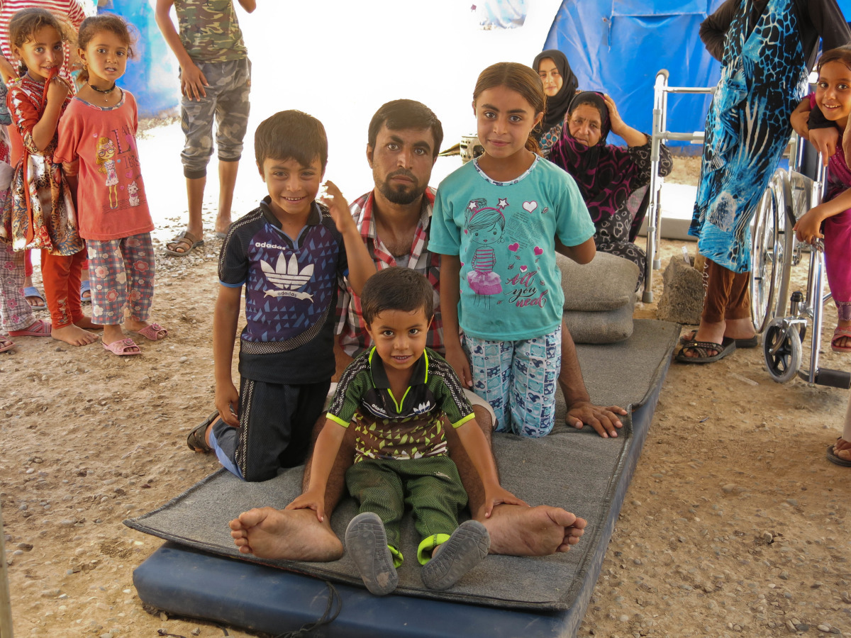 An injured Iraqi man sits on a mat at a IDP camp with his children on his lap.