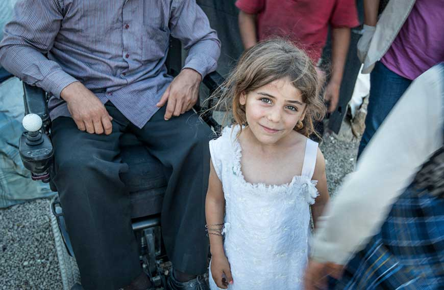 A young Syrian refugee stands in front of her father, who sits in a wheelchair, at a refugee camp in Lebanon.