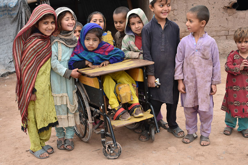 Samina, 7, sits in her wheelchair, surrounded by her friends in Pakistan.