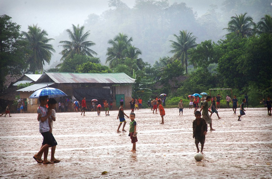 c_Wendy-Huyghe_Handicap-International__children_gather_on_a_rainy_muddy_soccer_field_in_a_refugee_camp_in_Thailand.jpg