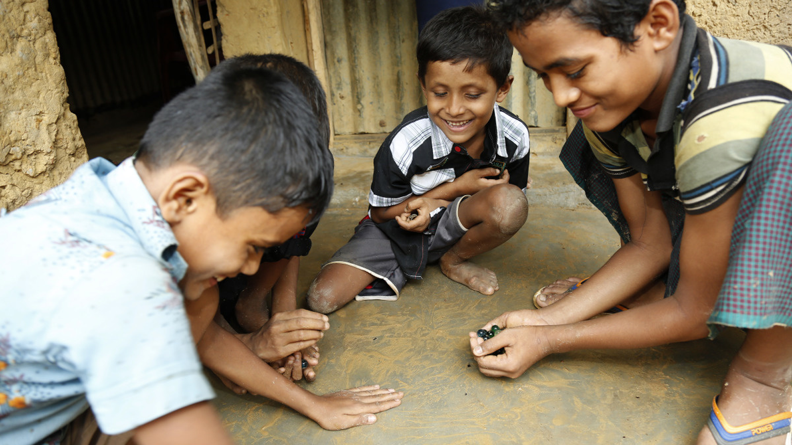 Refugee children in Bangladesh play with marbles