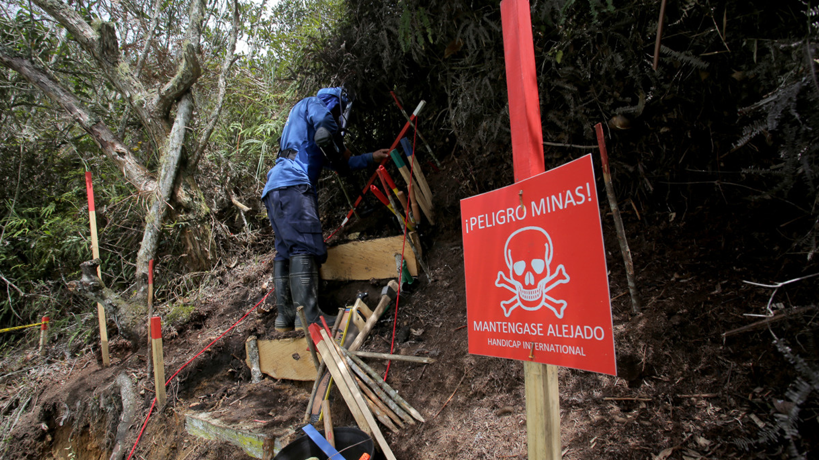 A deminer in Colombia looks for UXO on a steep hill