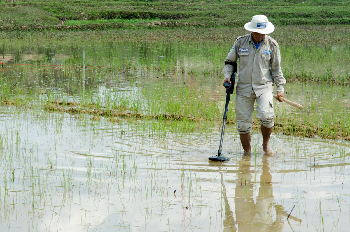 c_Sara-Goldberg_Handicap-International__A_deminer_in_Laos_looks_for_UXO_in_a_swamp.jpg