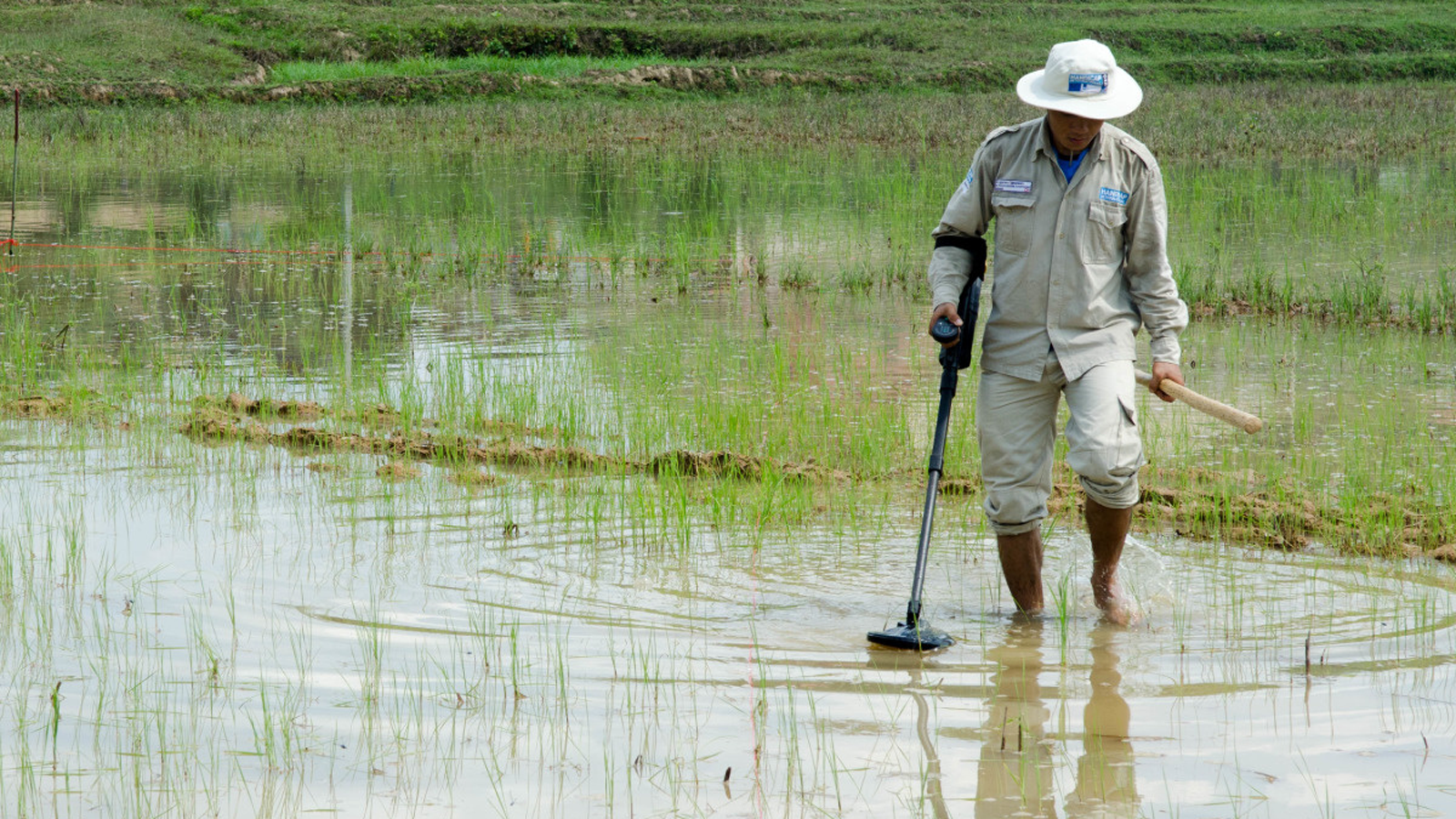 A deminer in Laos looks for UXO in a swamp