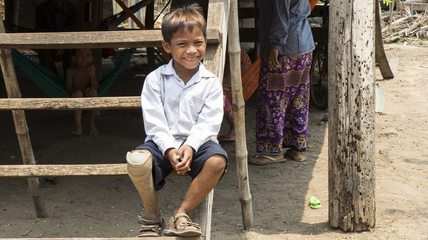 young boy sits smiling on wooden steps