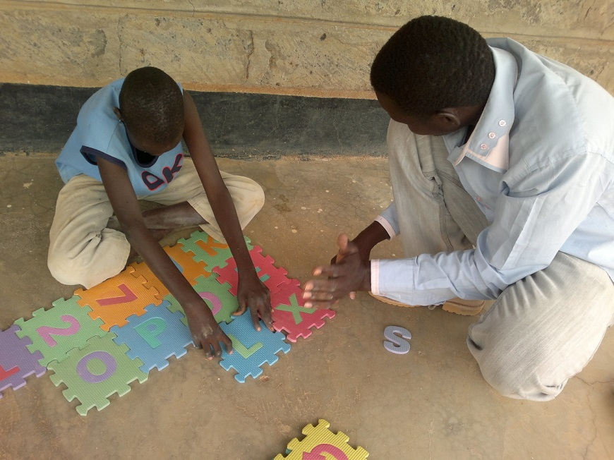c_Handicap-International__In_Daddab_camp_a_child_with_a_disability_practices_putting_a_puzzle_together_with_his_father.jpg