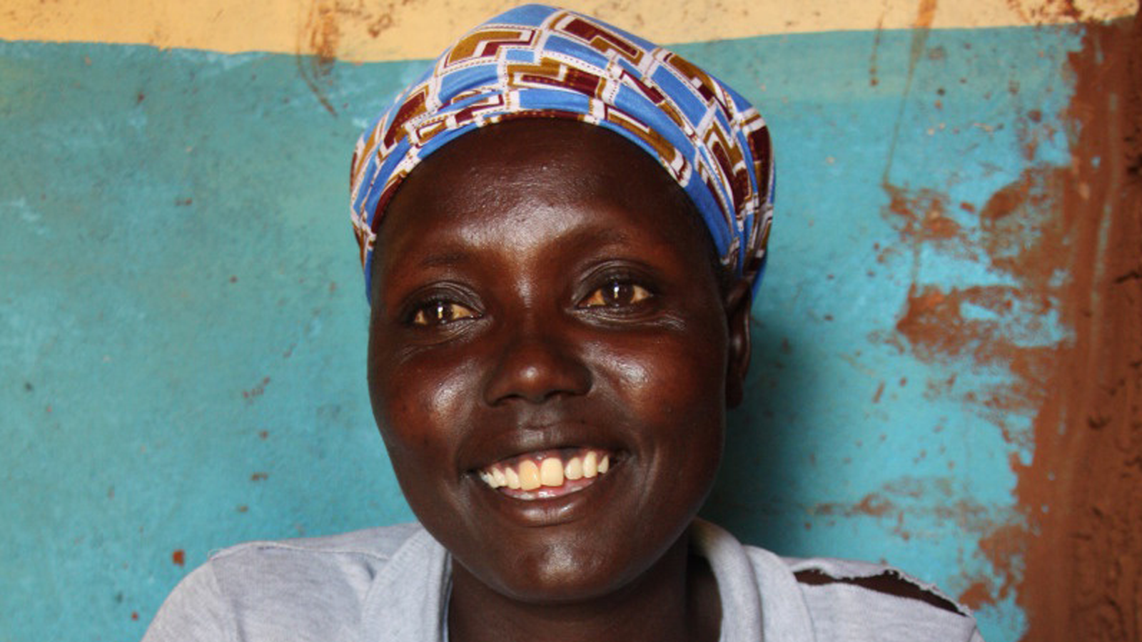 Christine sits and smiles at HI staff in Kenya