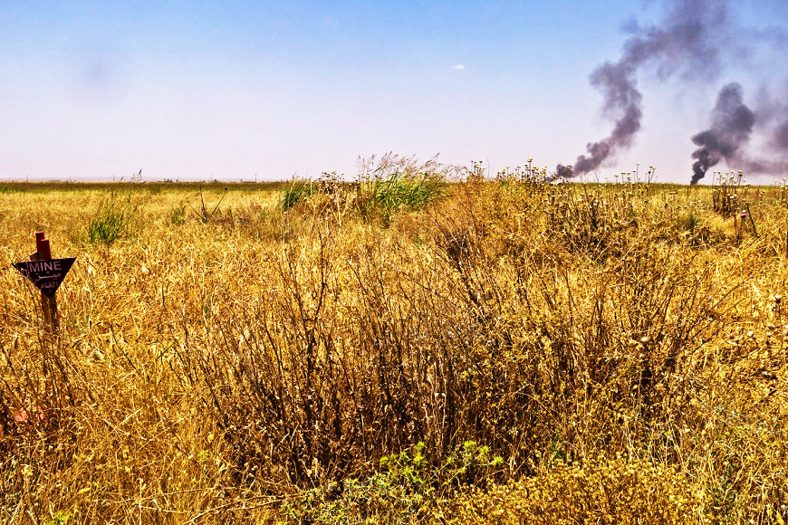 c_E-Fourt_Handicap-International_a_field_of_long_grass_with_a_mine_sign_has_smoke_rising_above_it.jpg