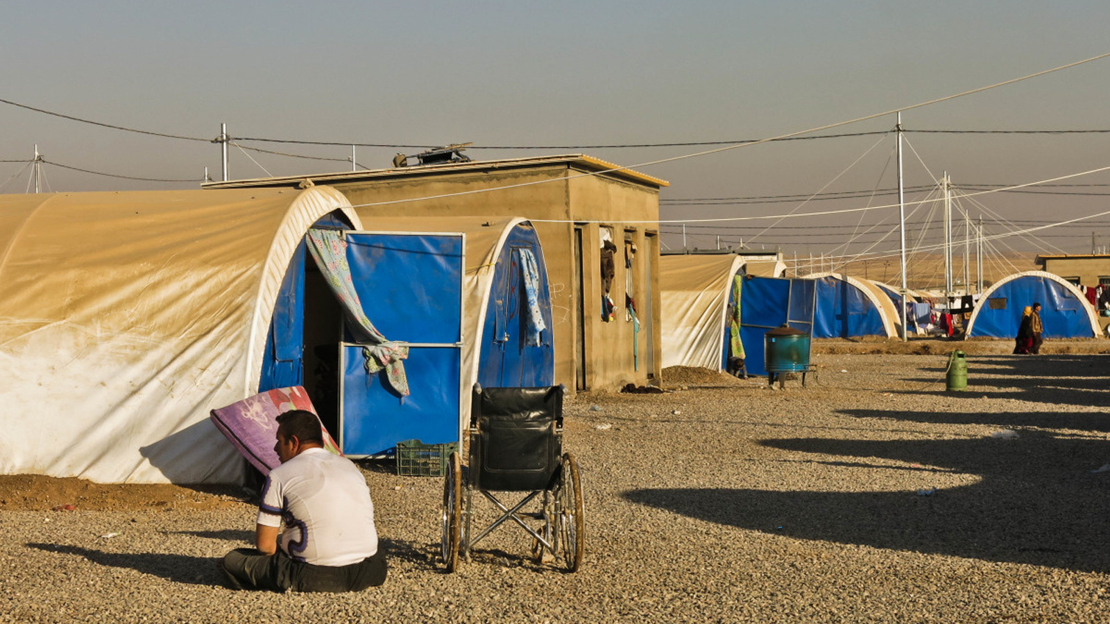 A man with disabilites sits on the ground at the Khazer camp in Iraq