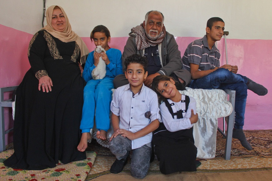 c_E-Fourt_Handicap-International__a_family_of_six_sits_against_a_pink_wall_facing_the_camera.jpg