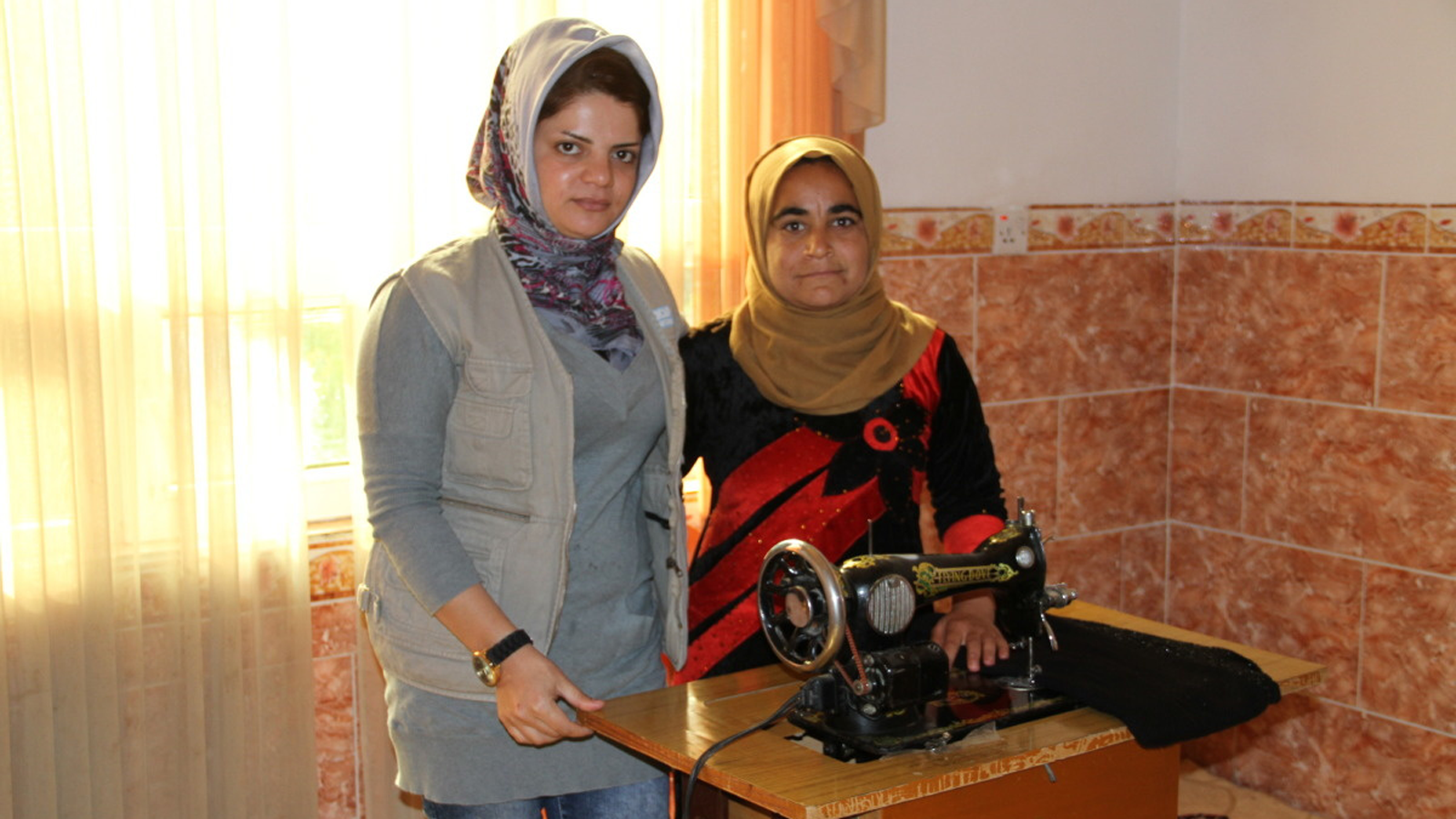 Payam stands with an HI staffer in front of her sewing machine in Iraq