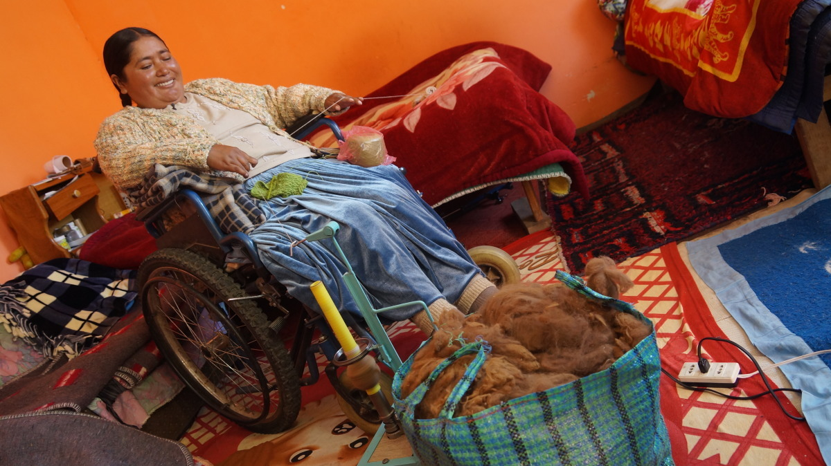 A woman in a wheelchair works with yarn in Bolivia