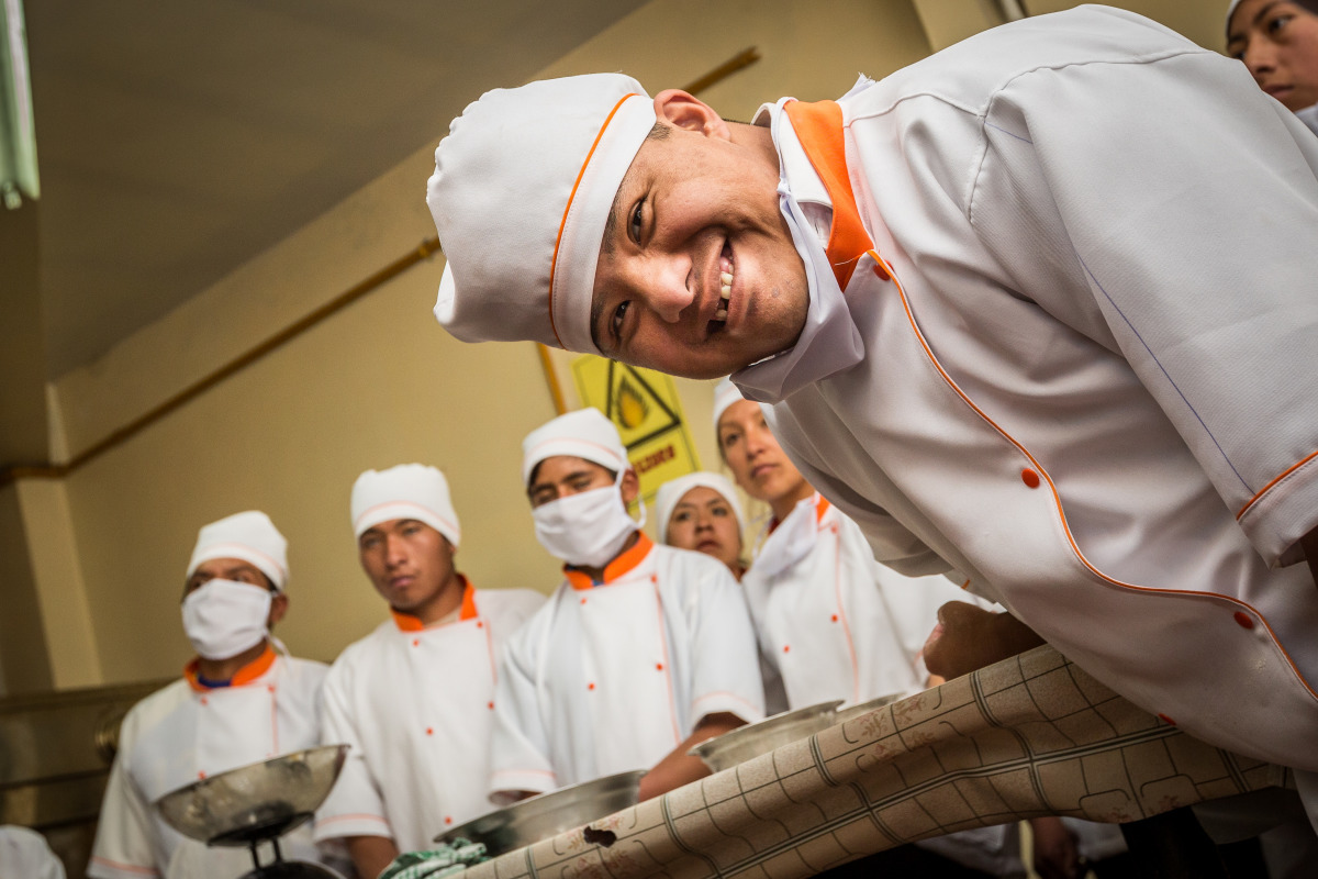 A man with a disability smiles into the camera as he participates in a bakery training program in Bolivia