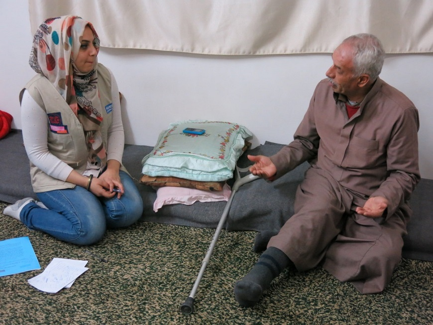 c_S-Sommella_Handicap-International__Physical_therapist_sits_on_the_floor_and_speaks_with_an_older_syrian_refugee.jpg