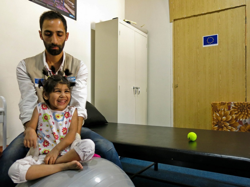 c_E-Fourt_Handicap-International_physical_therapist_balances_young_smiling_girl_on_exercise_ball.jpg