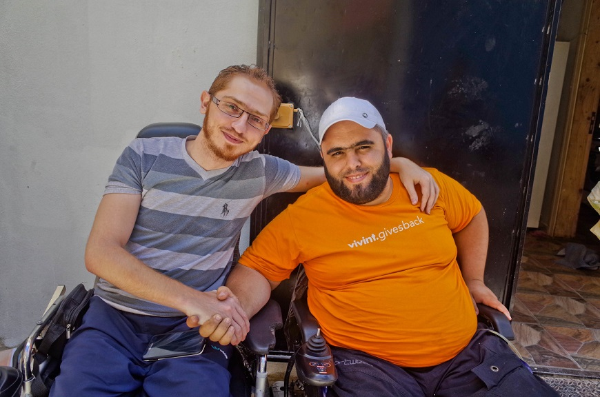 c_G-Vandendaelen_Handicap-International_two_men_in_wheelchairs_smile_and_hold_hands.jpg