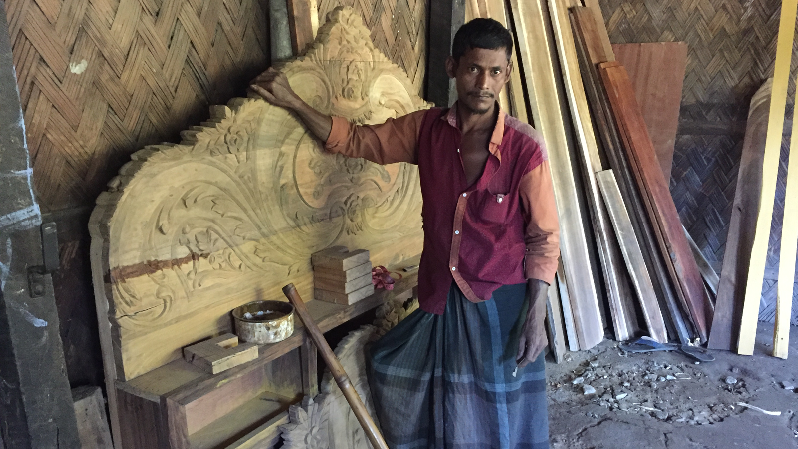 Abul stands in front of the headboard he made in Bangladesh