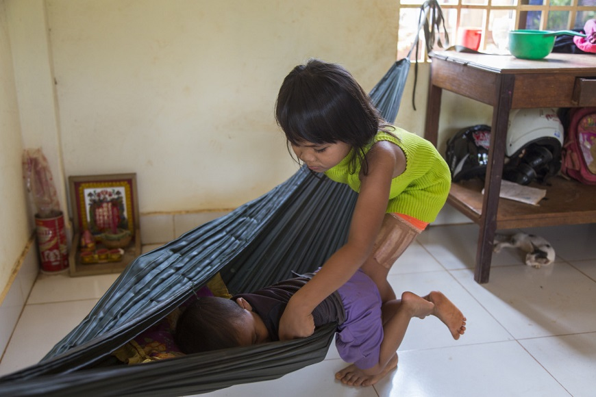 c_Soline-de-Groeve_Handicap-International_girl_with_one_arm_helps_toddler_into_hammock.jpg