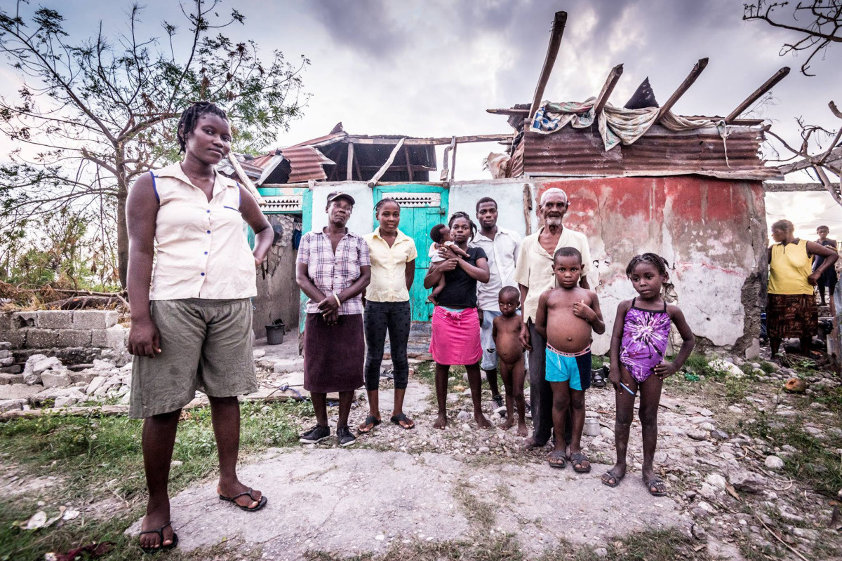 c_Benoit-Almeras_Handicap-International__Ines_and_her_family_standing_in_front_of_their_damaged_home_in_Haiti..JPEG