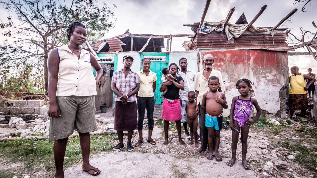 Ines and her family standing in front of their damaged home in Haiti