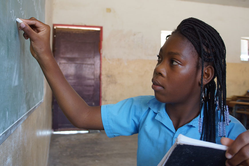Chelsia, 14, writes on a chalkboard at an inclusive school in Mozambique.