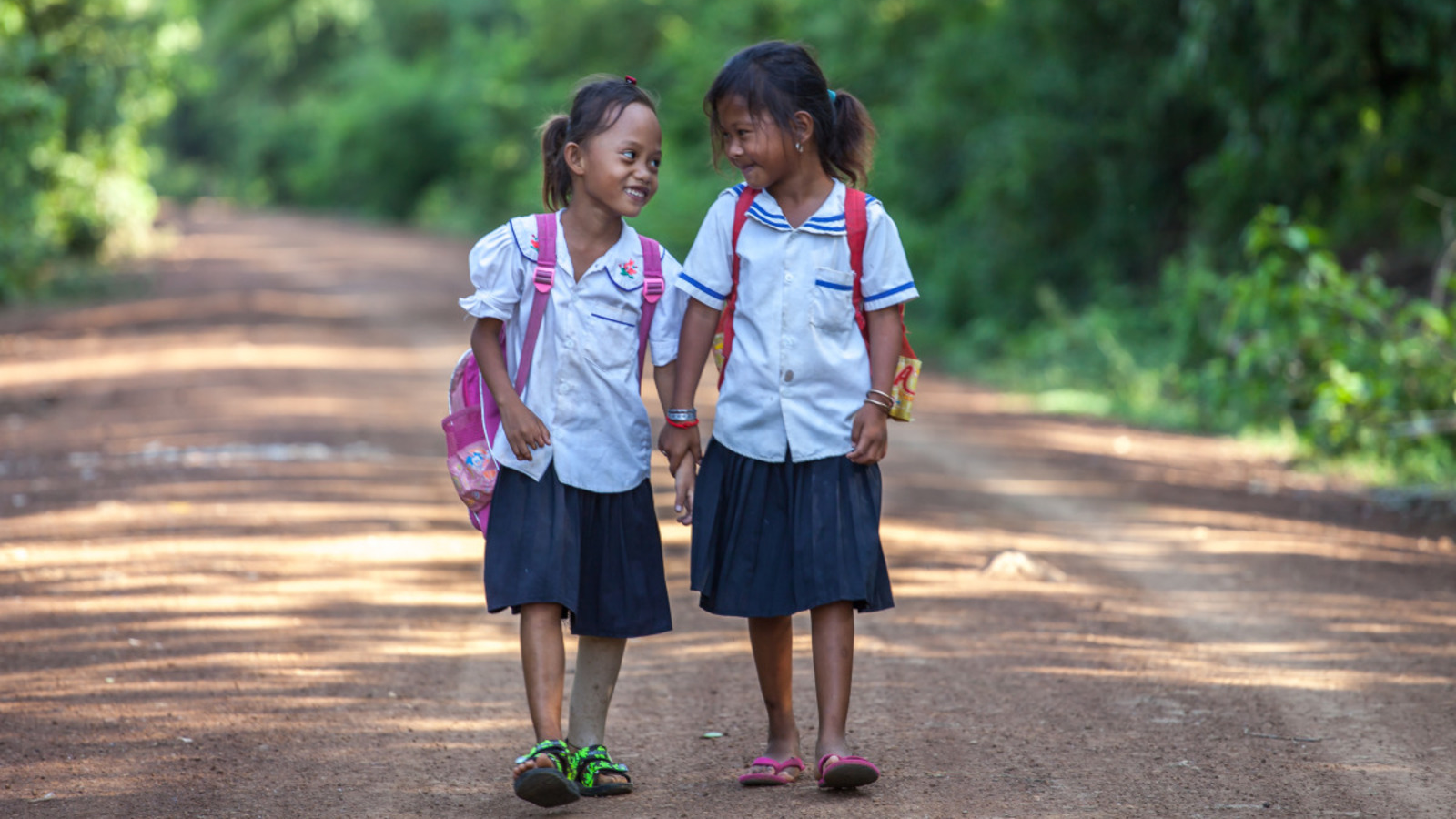 Channa walks to school with a friend in Cambodia