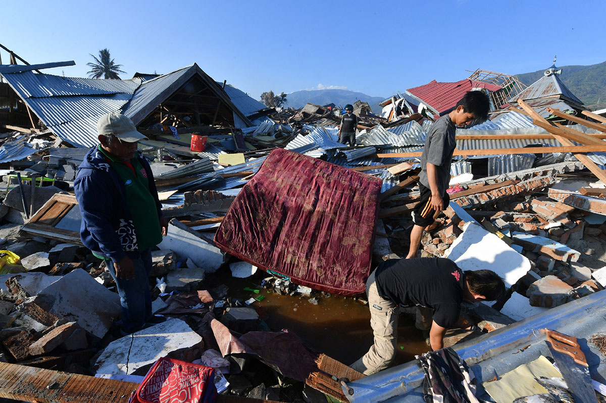 Indonesian men search for a family member at their damaged house in the Balaroa village in Palu on October the 1st 2018 after an earthquake and tsunami hit the area on September 28th
