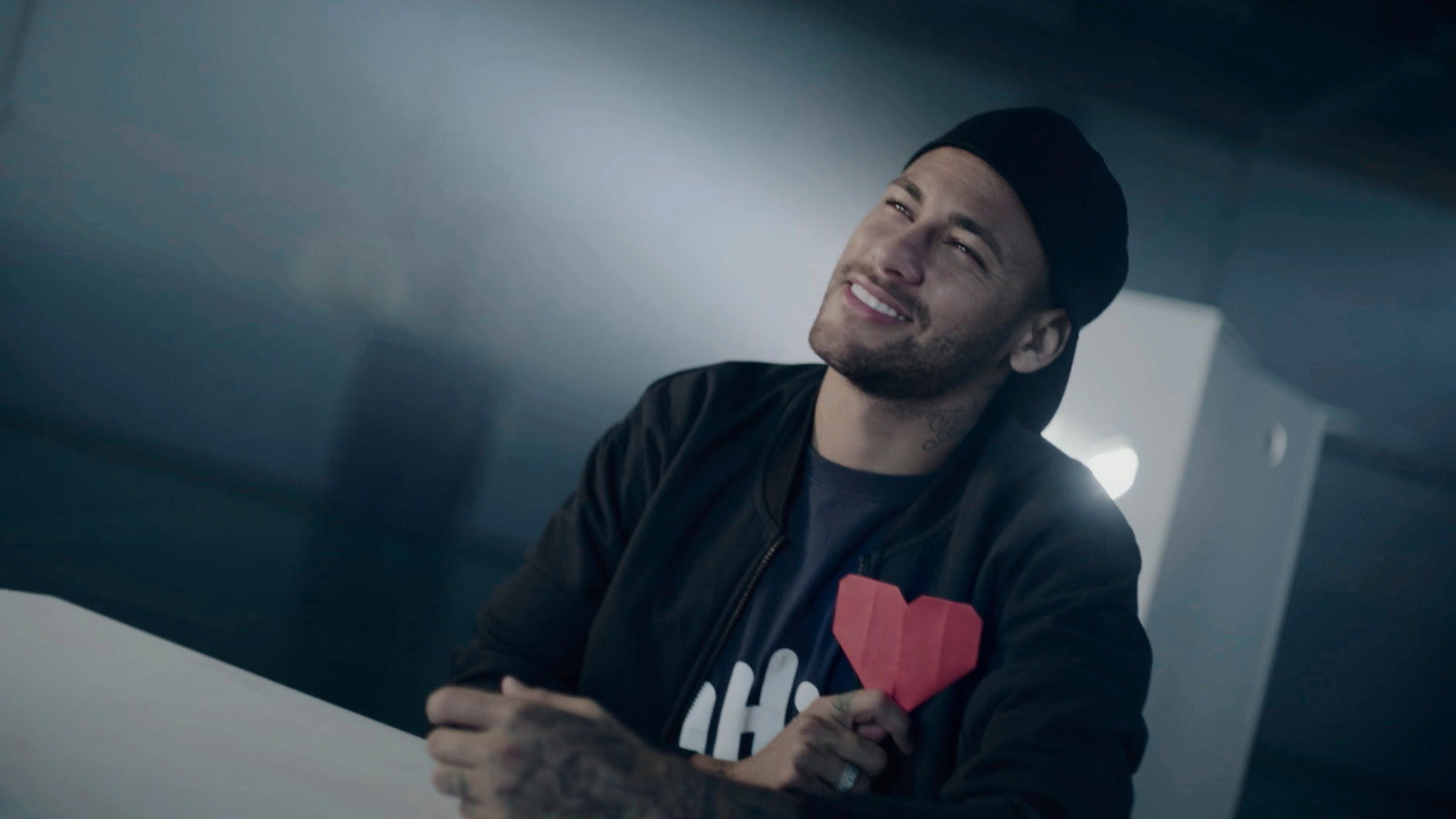"HI Global Ambassador Neymar Jr. holds a heart shaped origami up to his heart during the filming of ""Teacher Kids."""