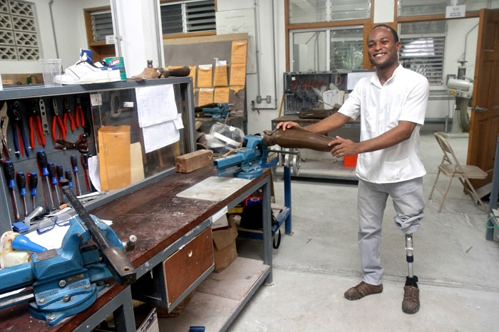 a Haitian with a lower limb prosthesis stands in the workshop where he creates bespoke limbs at Healing Hands for Haiti which was set up by HI