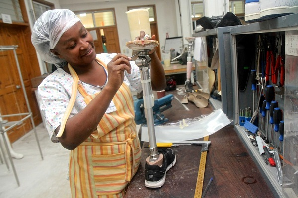 c_Nadia-Todres_HI__a_Haitian_woman_trained_by_HI_adjusts_the_hinge_of_a_prosthetic_leg_in_the_Healing_Hands_for_Haiti_workshop.jpg