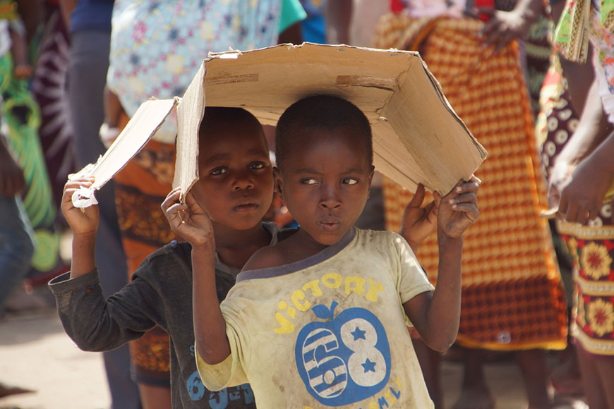 Two young boy carry a piece of cardboard in Mozambique following Cyclone Idai.