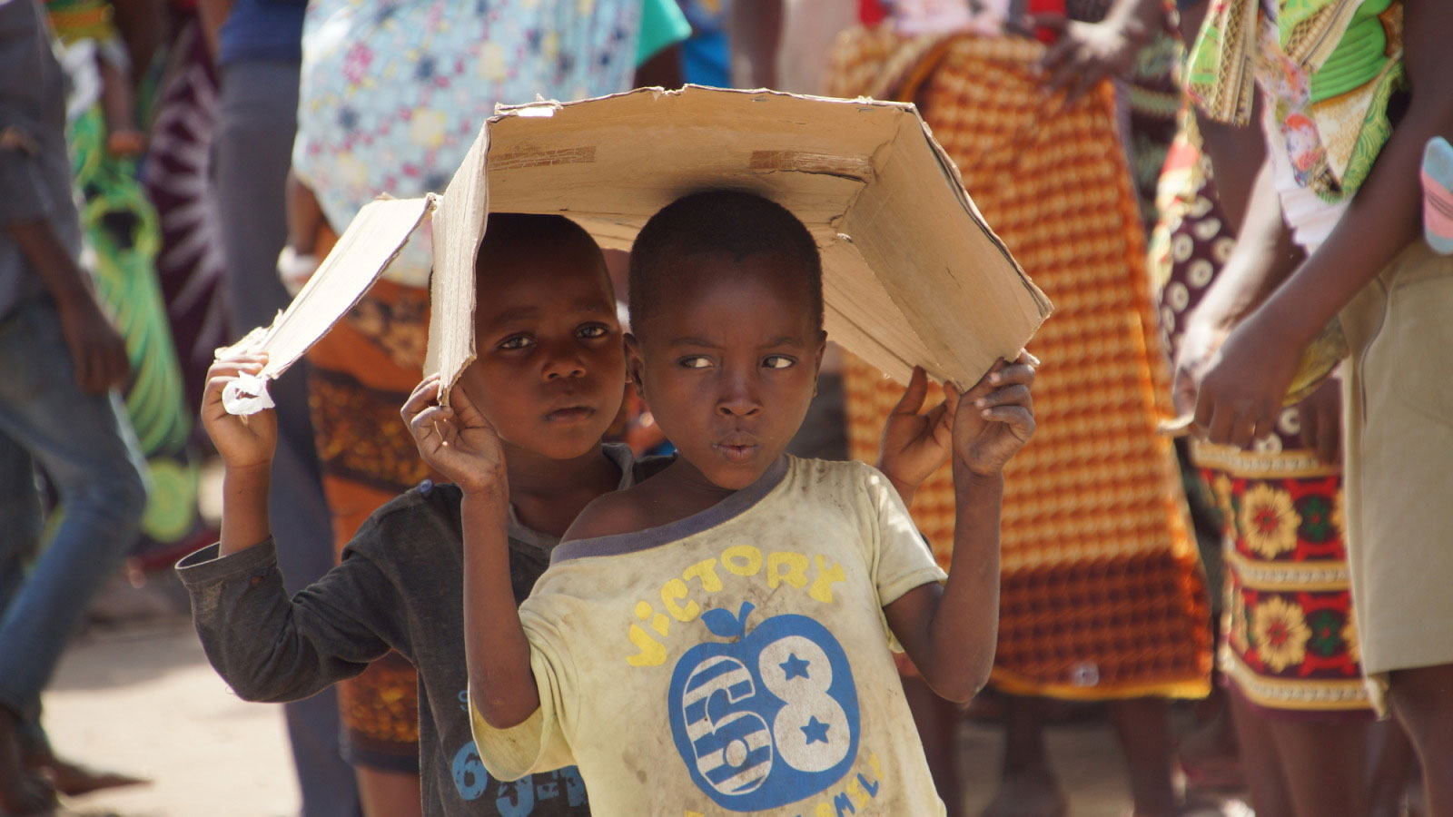 Two-young-boys-carrying-a-piece-of-cardbox-over-their-heads-in-Mozambique-following-Cyclone-Idai