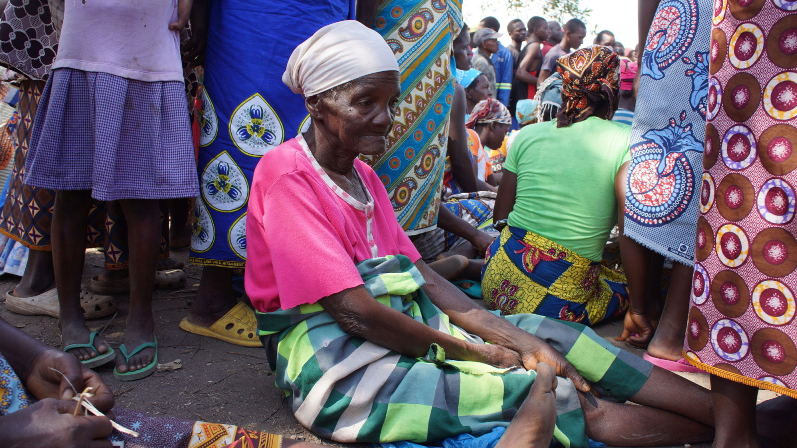 An-older-woman-sits-down-after-getting-tired-standing-in-a-line-for-humanitarian-aid-in-Mozambique