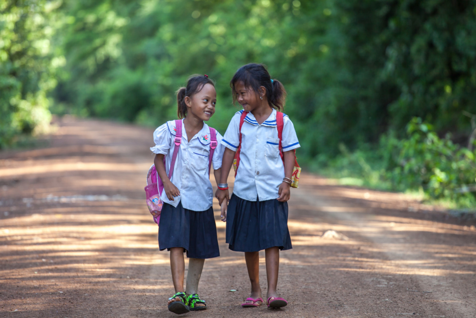 Channa walks with a friend to school in Cambodia