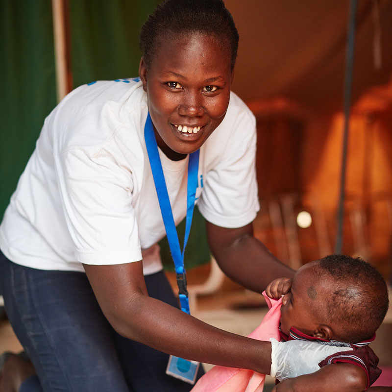 Grace, a physical therapist with HI, helps a baby with rehab exercises in Kenya's Kakuma refugee camp.