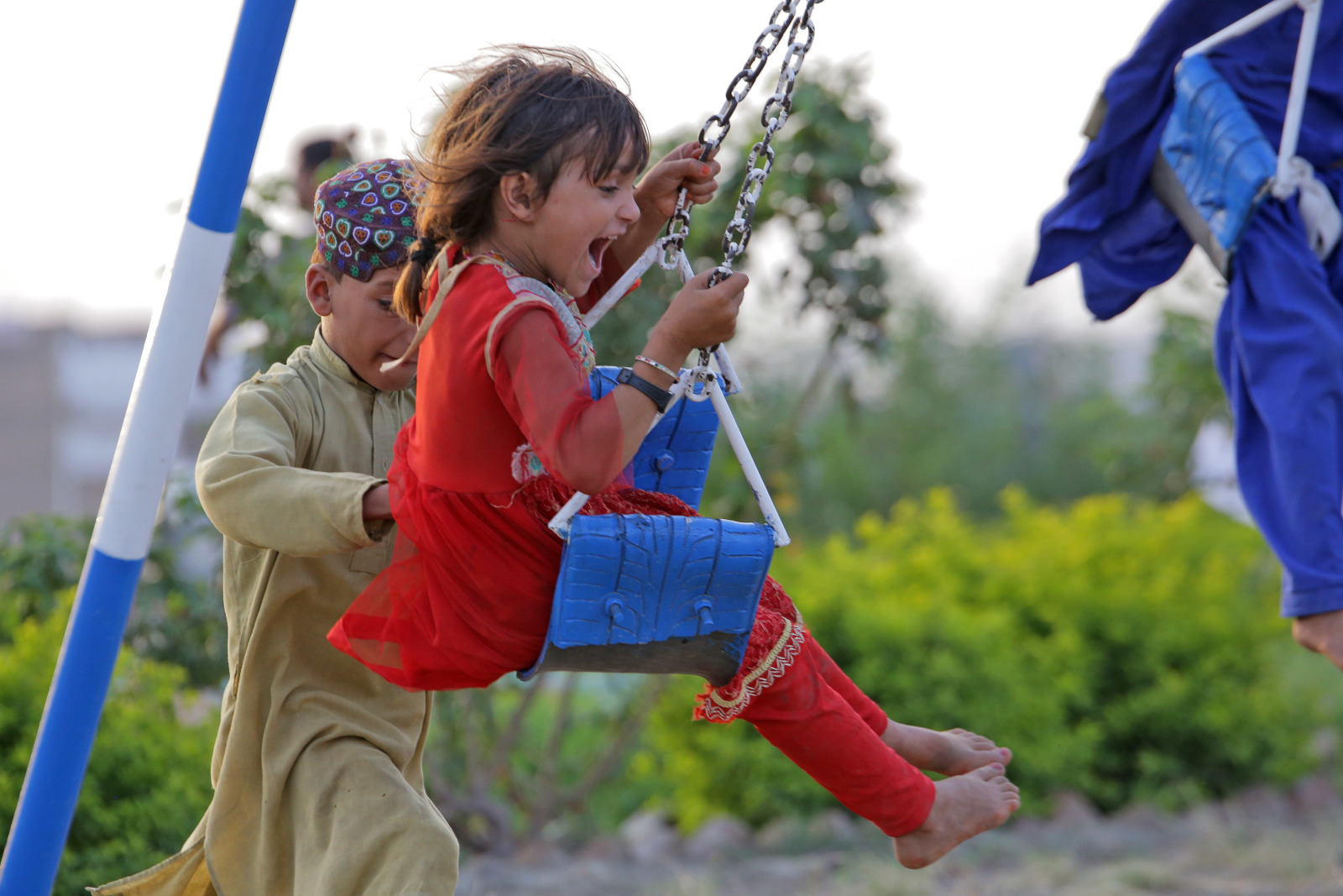 c_Dynimax-Intermedia_HI__A_little_girl_in_red_smiles_as_a_boy_pushes_her_on_swings.jpg