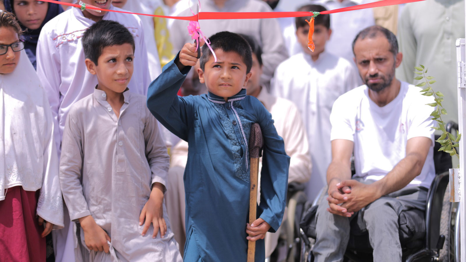 A boy using a crutch reaches to cut a red ribbon with a pair of black scissors a crowd of excited children and adults are behind him