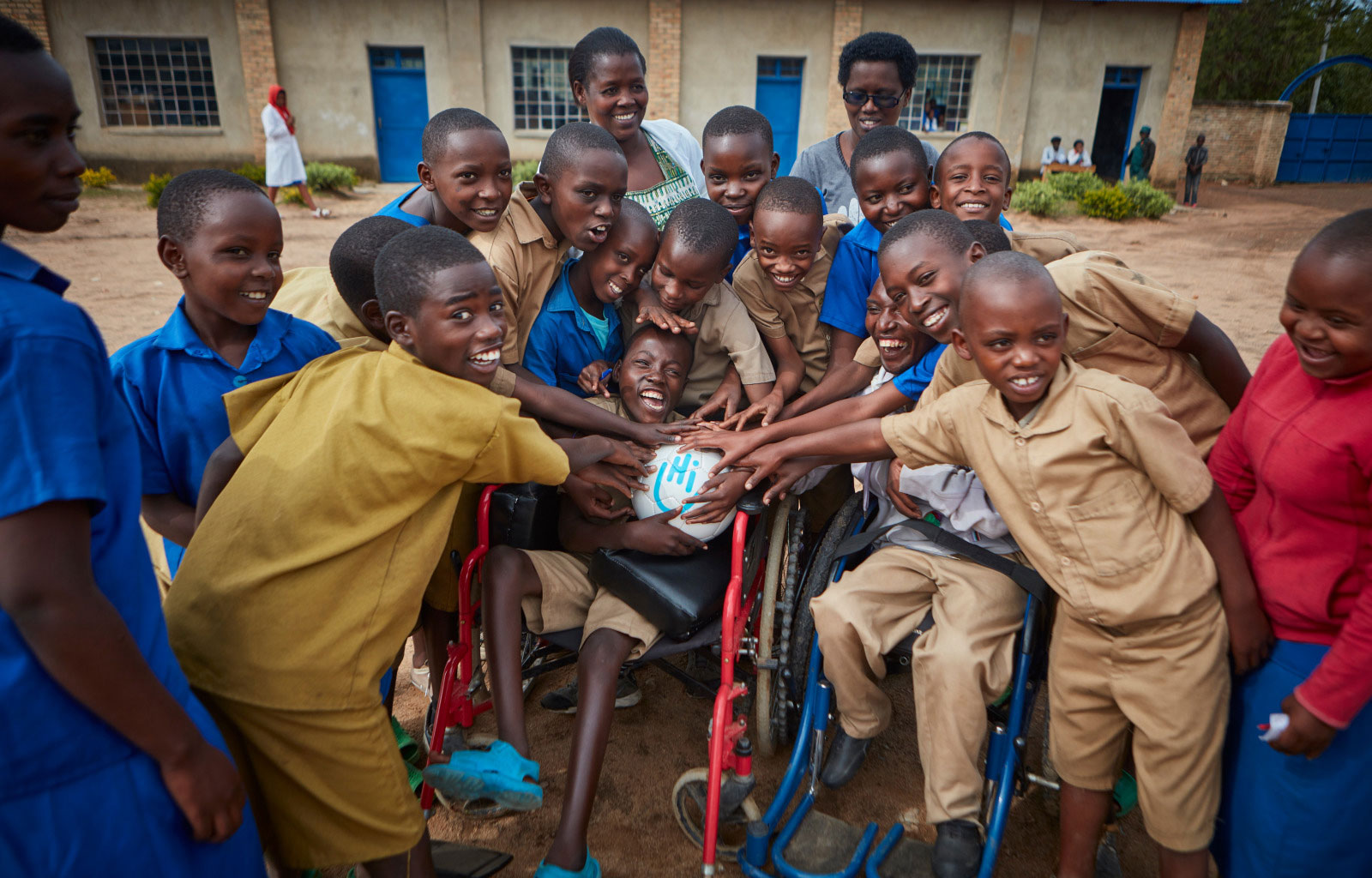 c_Neil-Thomas_HI__Emmanuel_-16_-who-has-cerebral-palsy_-holds-a-soccer-ball-and-is-surrounded-by-friends-at-a-school-in-Rwanda.jpg