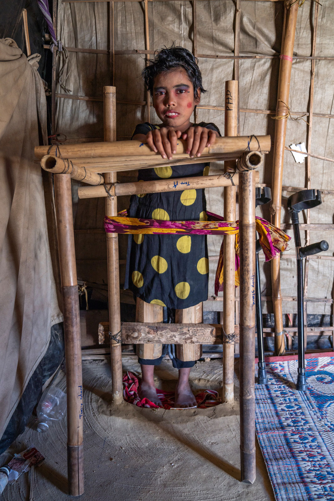 c_Abir-Abdullah_HI__Samira_-10_-who-has-cerebral-palsy_-stands-with-support-from-a-bamboo-frame-build-by-an-HI-physical-therapist.jpg