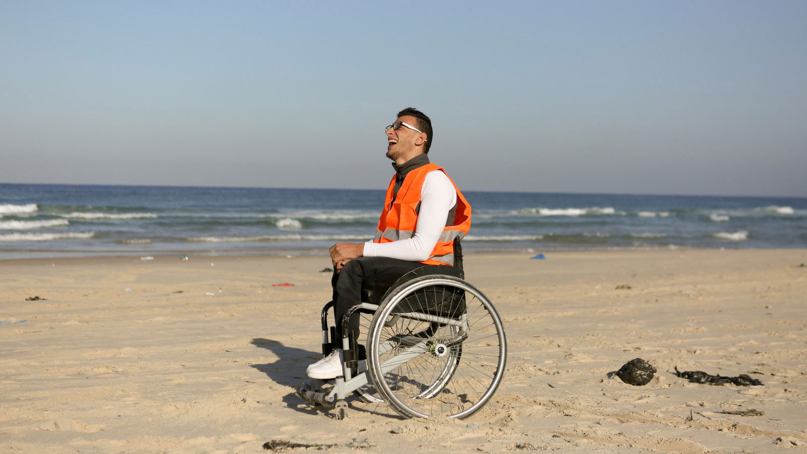 Ali -who-enjoys-the-new-inclusive-beach-in-Gaza -smiles-while-in-his-wheelchair-on-the-sand