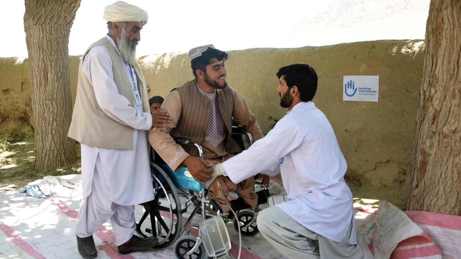 Hazrat-smiles-in-his-wheelchair-while-being-supported-by-a-physical-therapist-with-Humanity- -Inclusion-in-Afghanistan