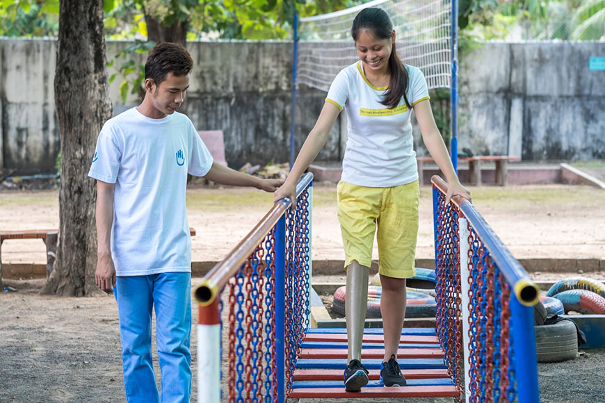 Kanha, 18, walks on her newly-fit prosthetic leg with support from a physical therapist from Humanity & Inclusion in Cambodia.