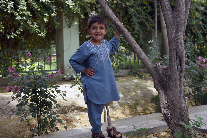 Sanaullah, 5, stands tall in a garden in Afghanistan on his new prosthetic leg.