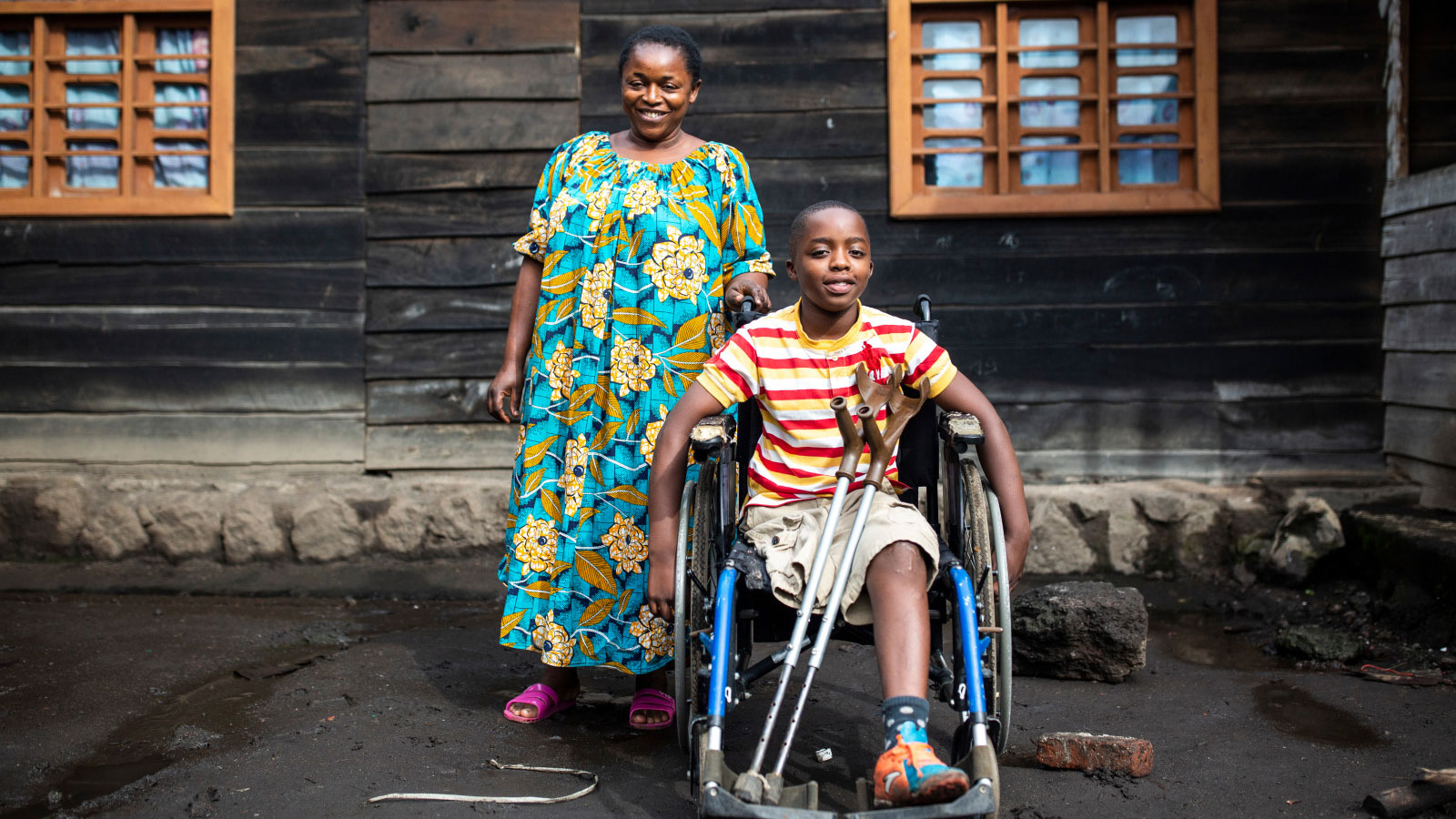 Philemon-smiles-in-his-wheelchair-next-to-his-mother-who-is-standing-next-to-him-in-the-DRC