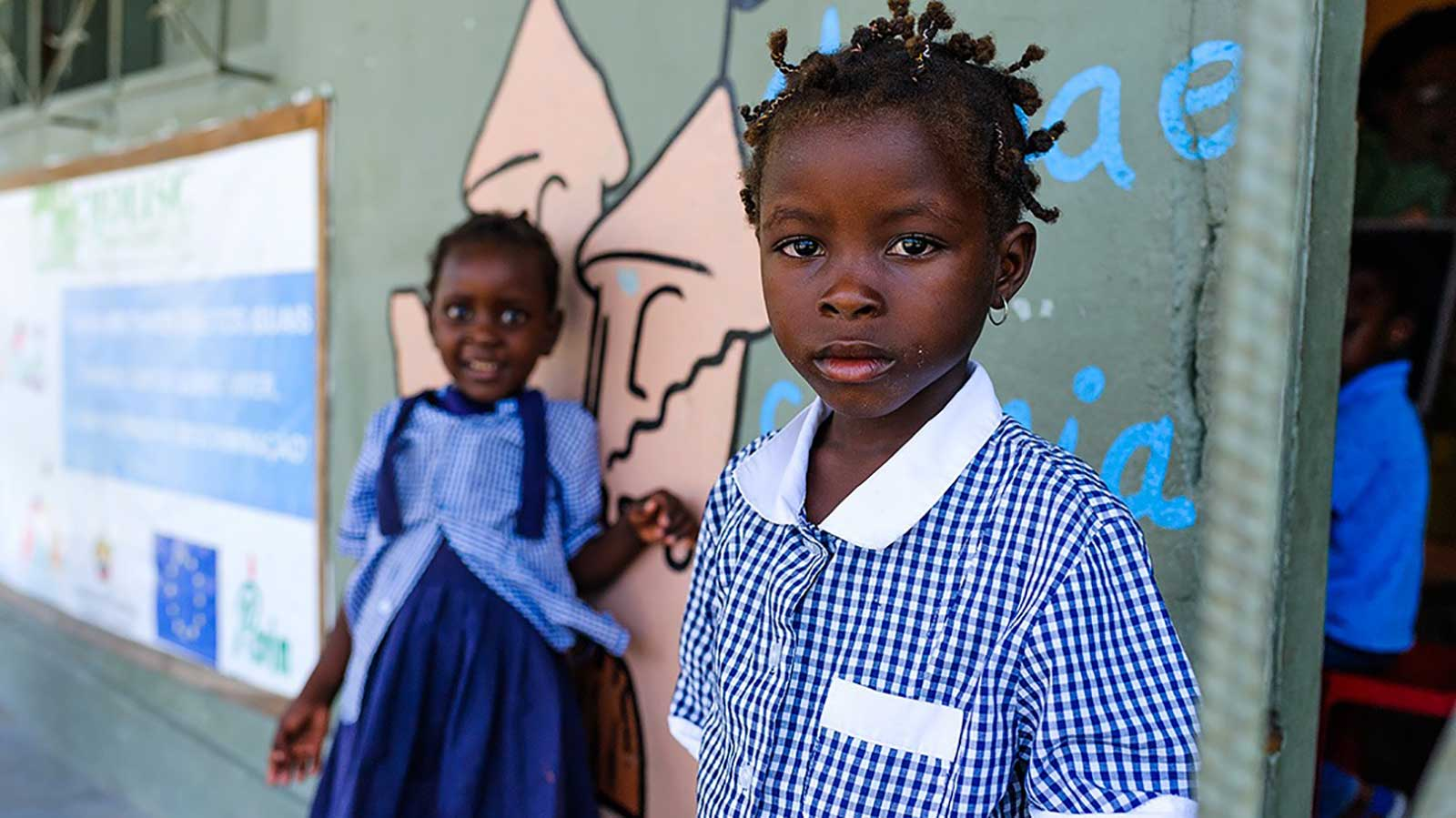 Two-preschoolers-in-Mozambique-stand-against-their-school-which-was-rebuilt-after-Cyclone-Idai